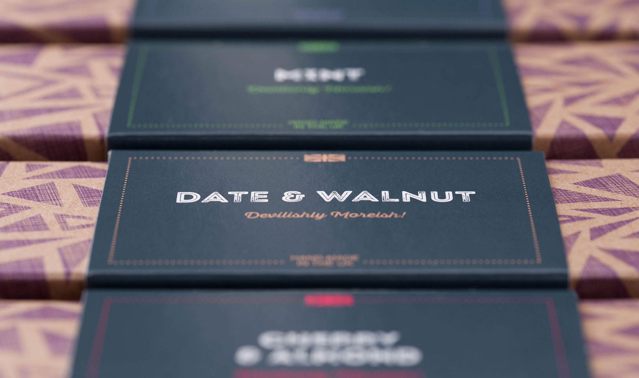 Chocolate packaging design. Image shot of the top of the cartons lined up. Shallow depth of field with the focus on the flavour name. Designed by packaging design agency - Flipflop Design Ltd.
