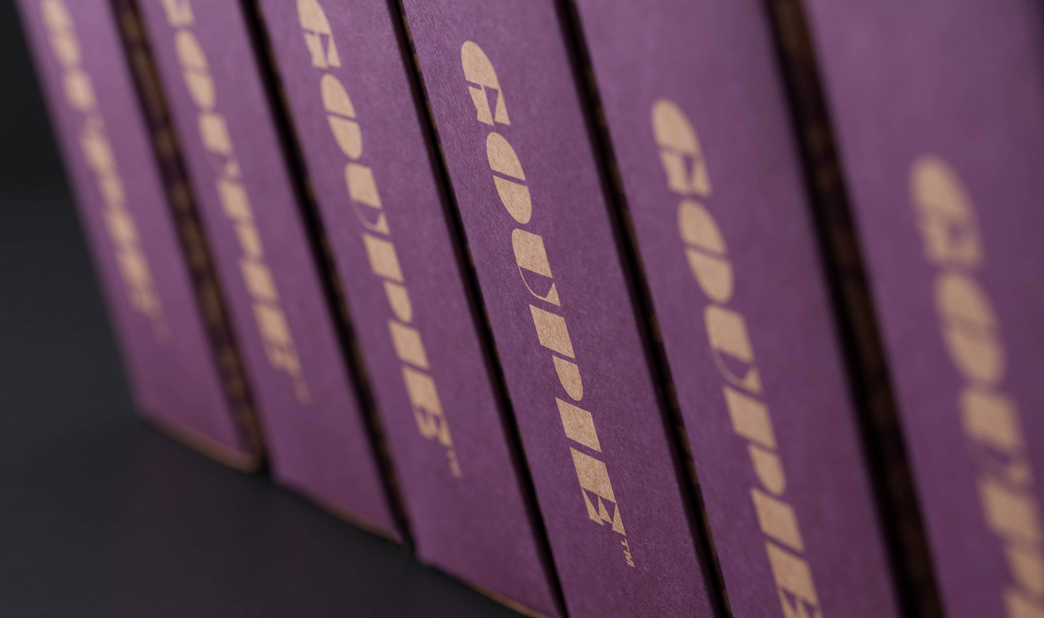 Chocolate packaging design. Image shot of the sides of the trapezoid cartons lined up. Shallow depth of field with the focus on the brand name. Designed by packaging design agency - Flipflop Design Ltd.