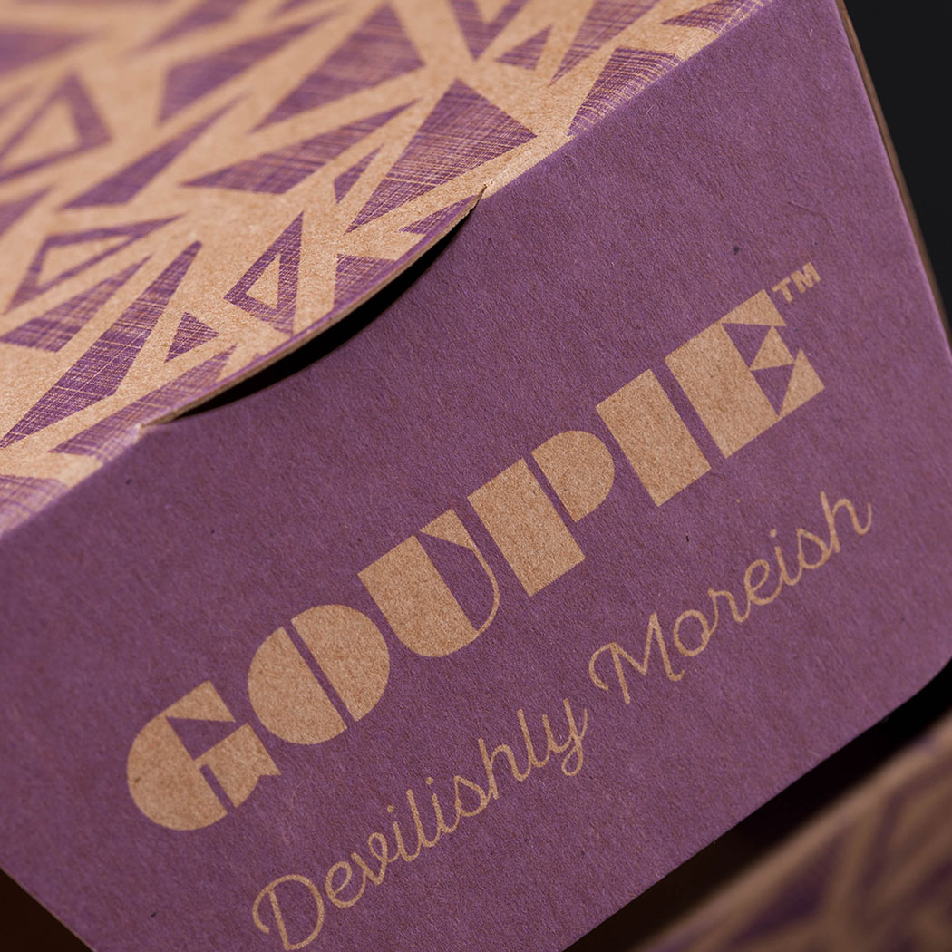 Chocolate packaging design. Tightly cropped image shot of the inside flap of new trapezoid carton. Shallow depth of field with the focus on the Goupie brand logo. Designed by packaging design agency - Flipflop Design Ltd.