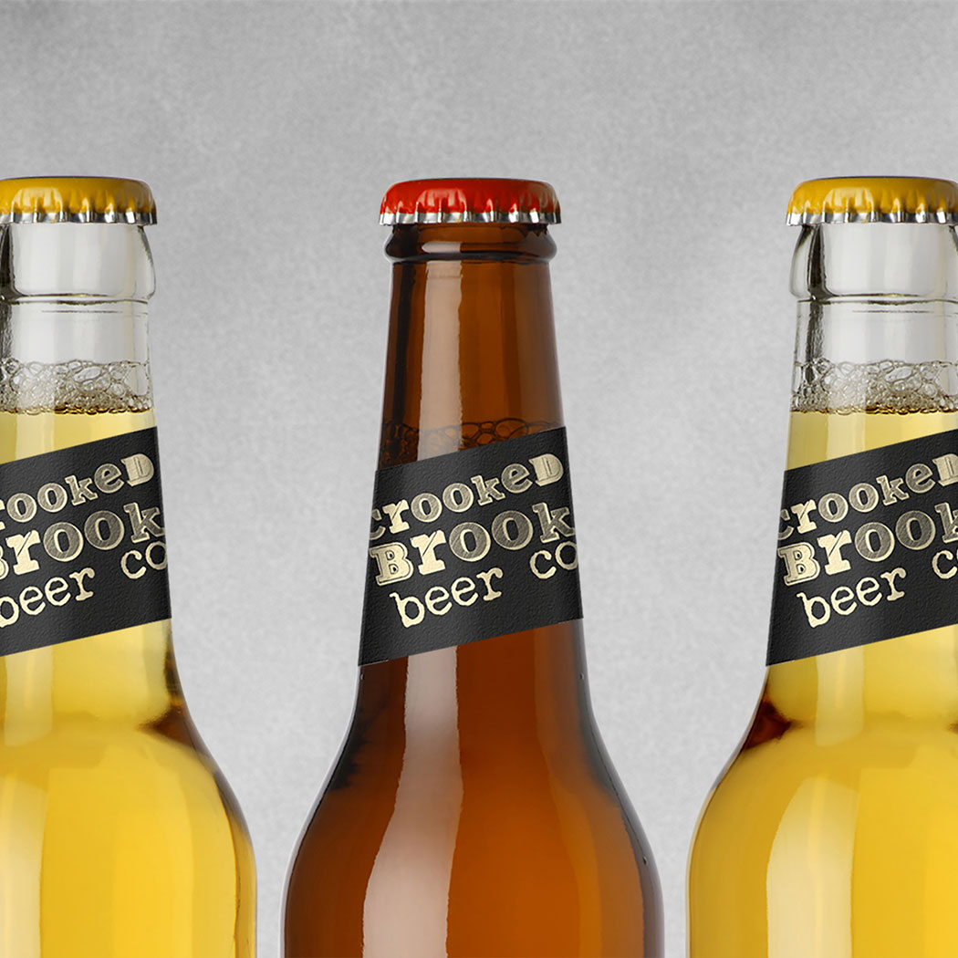 Craft beer packaging design for the brand Crooked Brook. Close up image of 3 beer necks, lined up with concrete backdrop. Designed by packaging design agency - Flipflop Design.