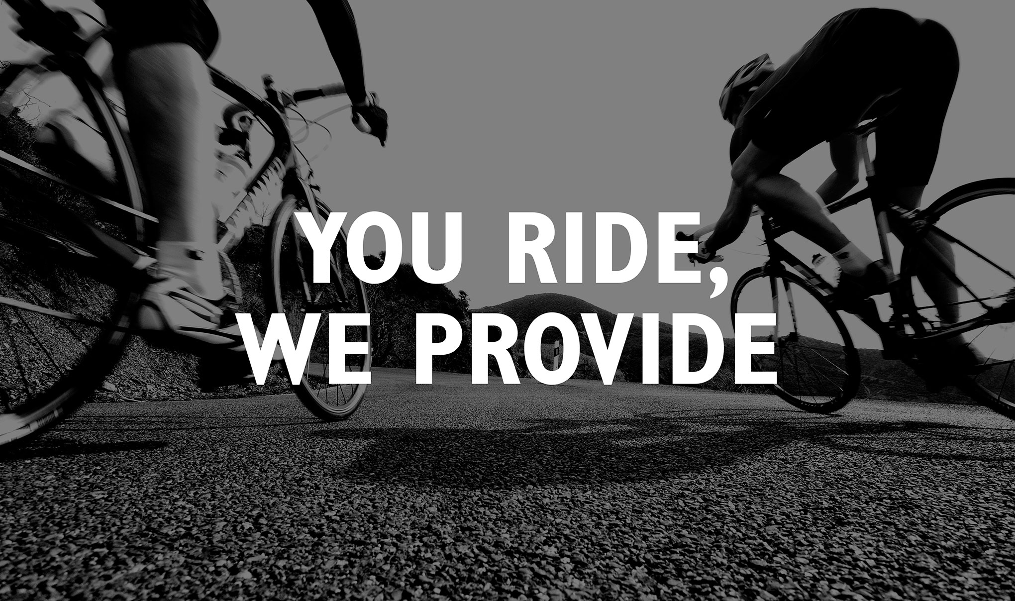Text ' You Ride, We Provide' written in white over a black & white image of two cyclists.